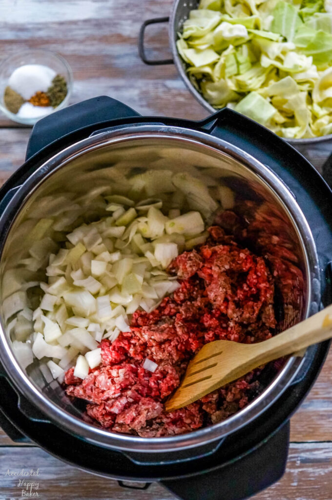 Ground beef is browned with onion and garlic in the instant pot.