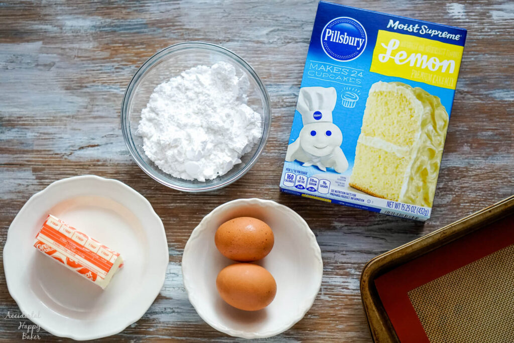 The ingredients needed for the recipe: butter, powdered sugar, eggs, and a box of lemon cake mix.