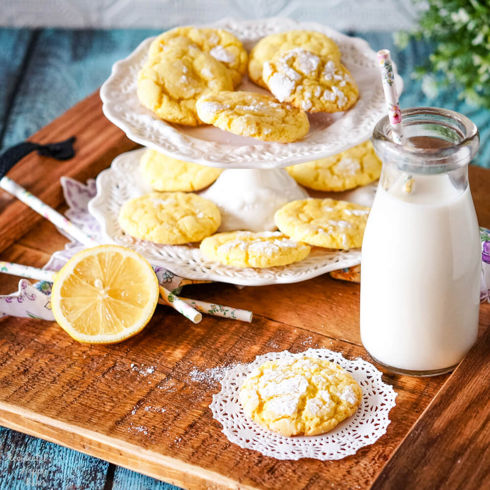 A wooden tray holding a plate of lemon crinkle cookies, a glass milk bottle and a sliced lemon.