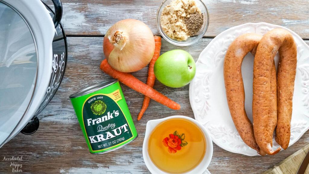 The ingredients needed for this recipe; sauerkraut, kielbasa, carrots, apple, onion, brown sugar, caraway seeds and apple juice.
