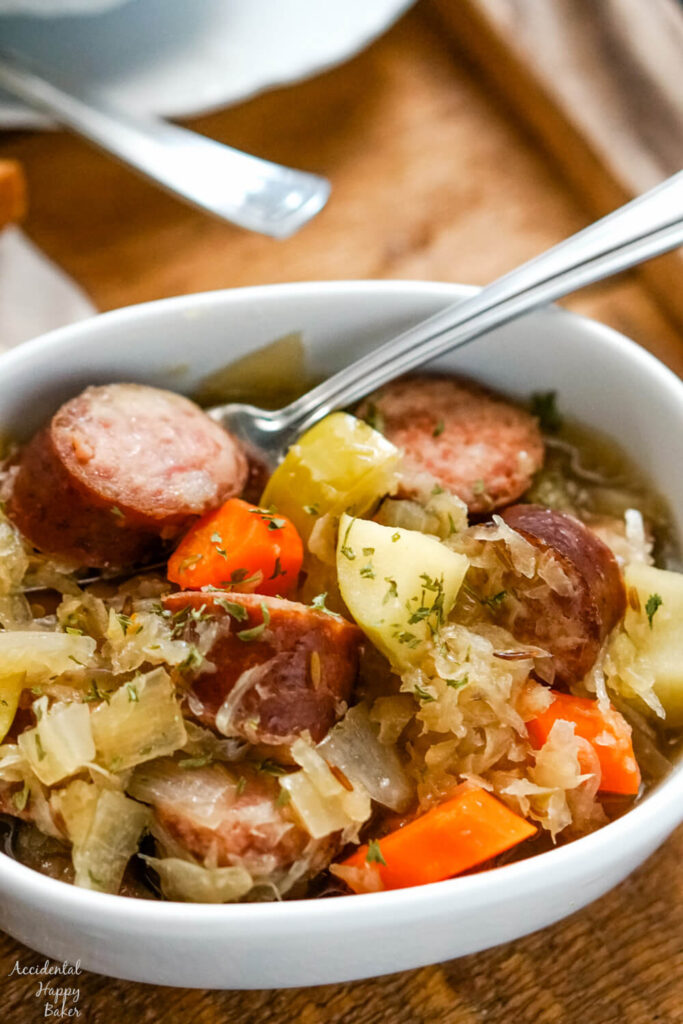 A white bowl of slow cooker kielbasa and sauerkraut on a wooden tray.
