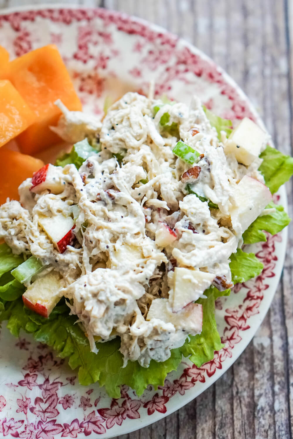 apple pecan chicken salad on a bed of lettuce with fruit on a floral plate