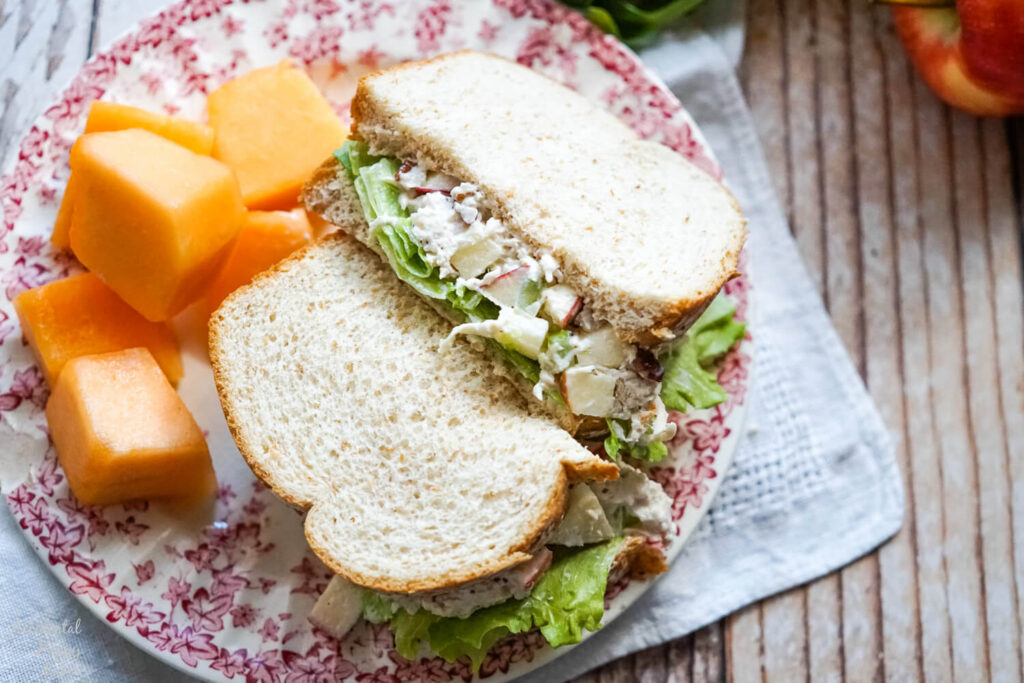apple pecan chicken salad sandwich with a side of fruit on a floral plate