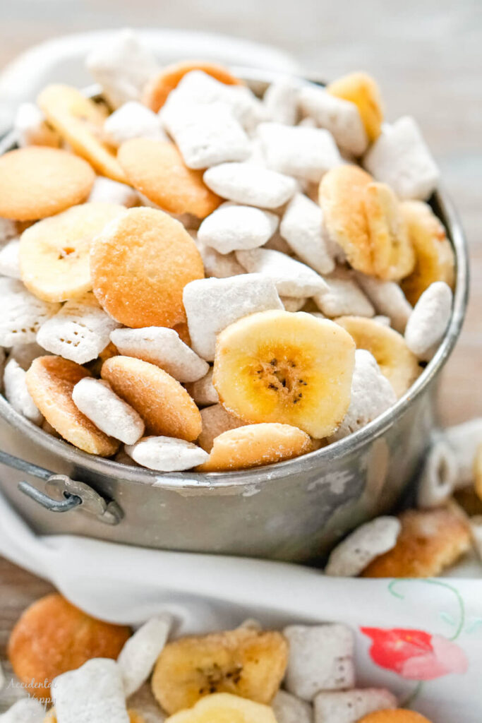 A metal bucket full of banana chips, mini vanilla wafer cookies and banana cream pie flavored cereal pieces.