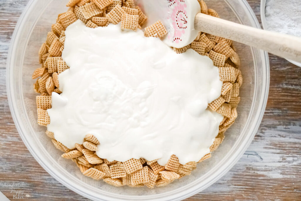 A bowl of chex cereal with melted almond bark poured over it.