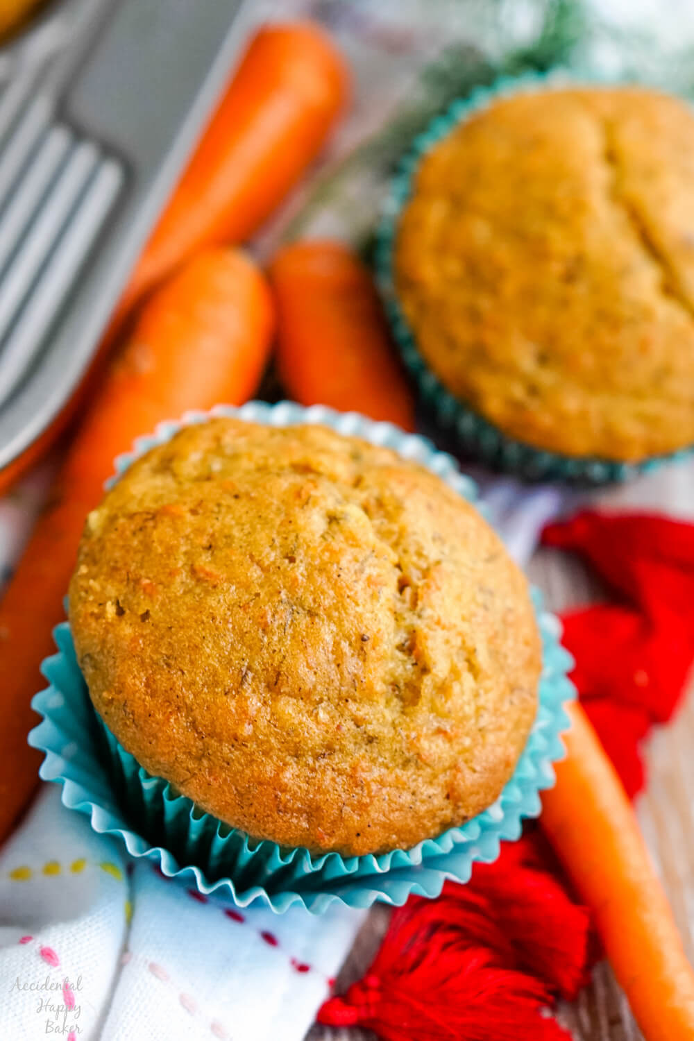 carrot banana muffin in cupcake liner with carrot beside it