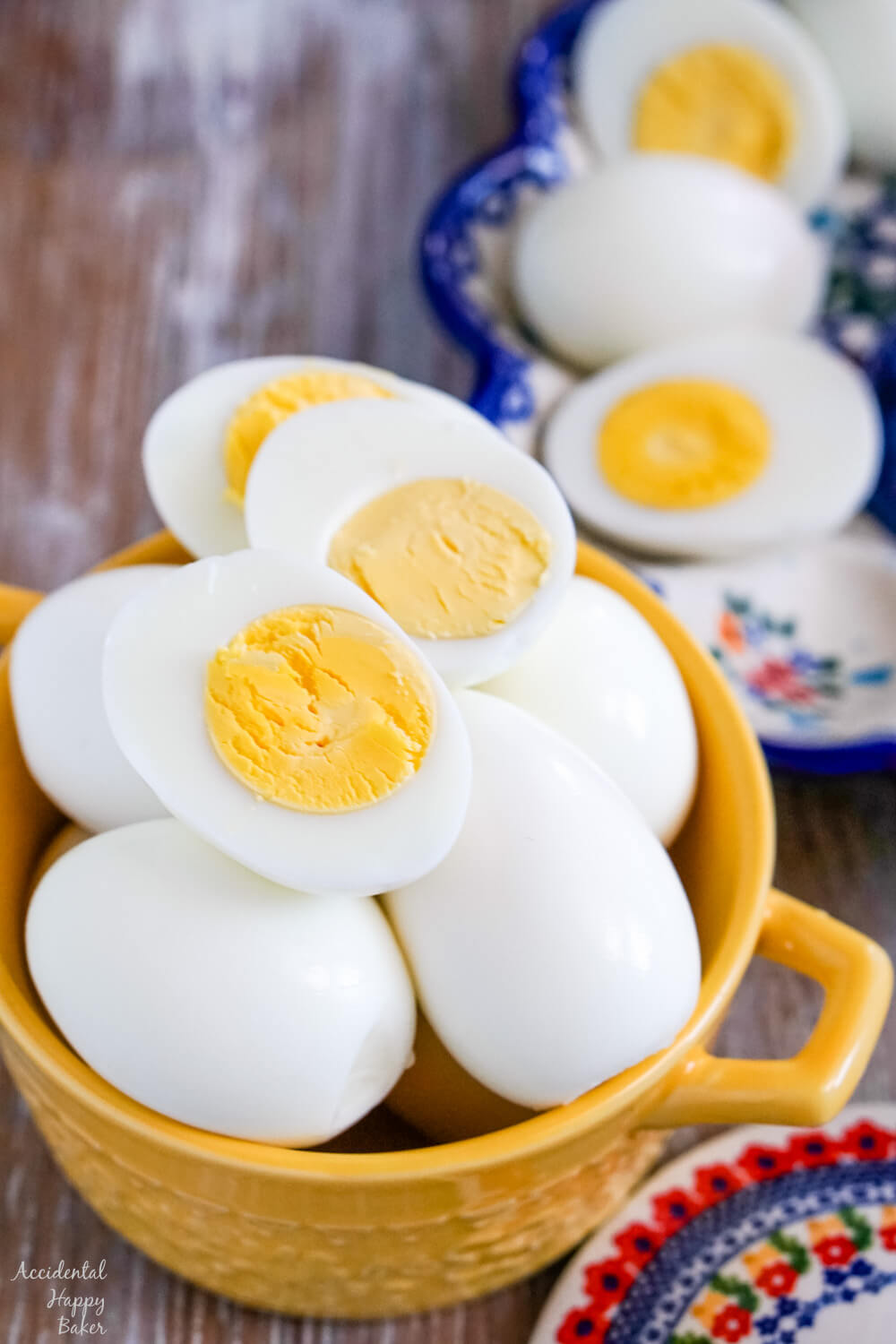 A yellow bowl full of hard boiled eggs, with a few sliced hard boiled eggs laying on top.
