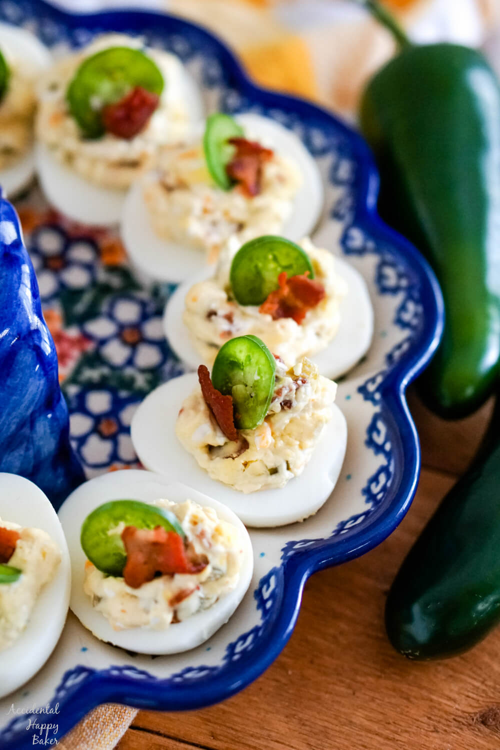 A plate of jalapeno popper deviled eggs garnished with slices of jalapenos sitting next to jalapeno peppers.