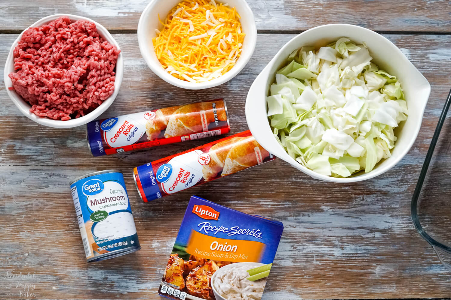 The ingredients needed to make Runza casserole; crescent rolls, ground beef, cabbage, cheese, onion soup mix, and cream of mushroom soup.