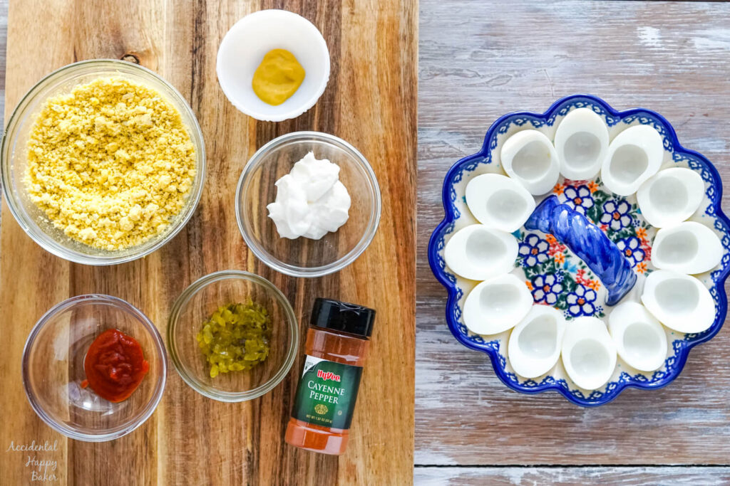 Ingredients in separate bowls on a cutting board, next to cooked egg whites in a egg dish.
