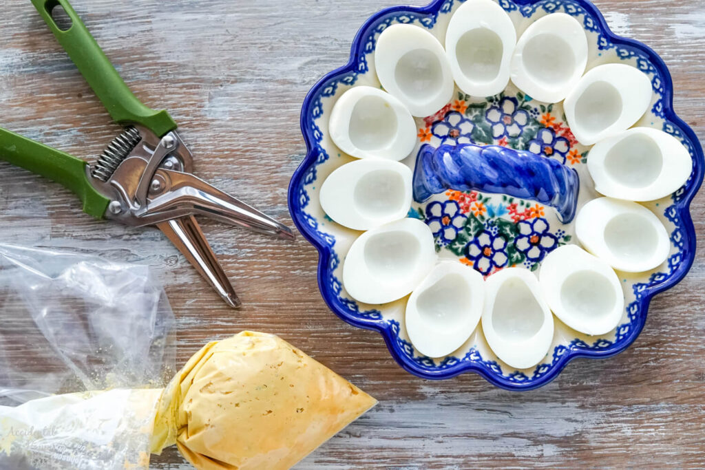 Filling ingredients in a Ziploc bag, and egg whites in a floral deviled egg dish.