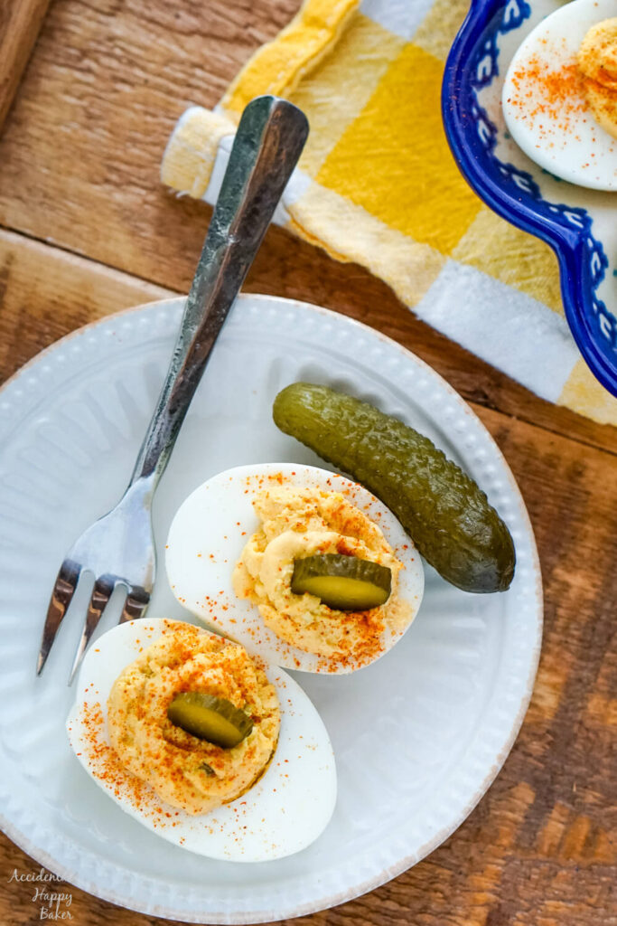 Deviled egg topped with a slice of pickle on a white plate with a fork.