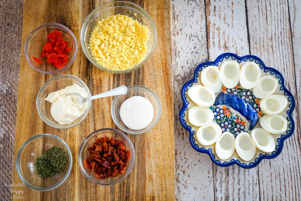 The ingredients needed for BLT deviled eggs: hard boiled eggs, tomatoes, mayo, ranch, chives, parsley, and bacon.