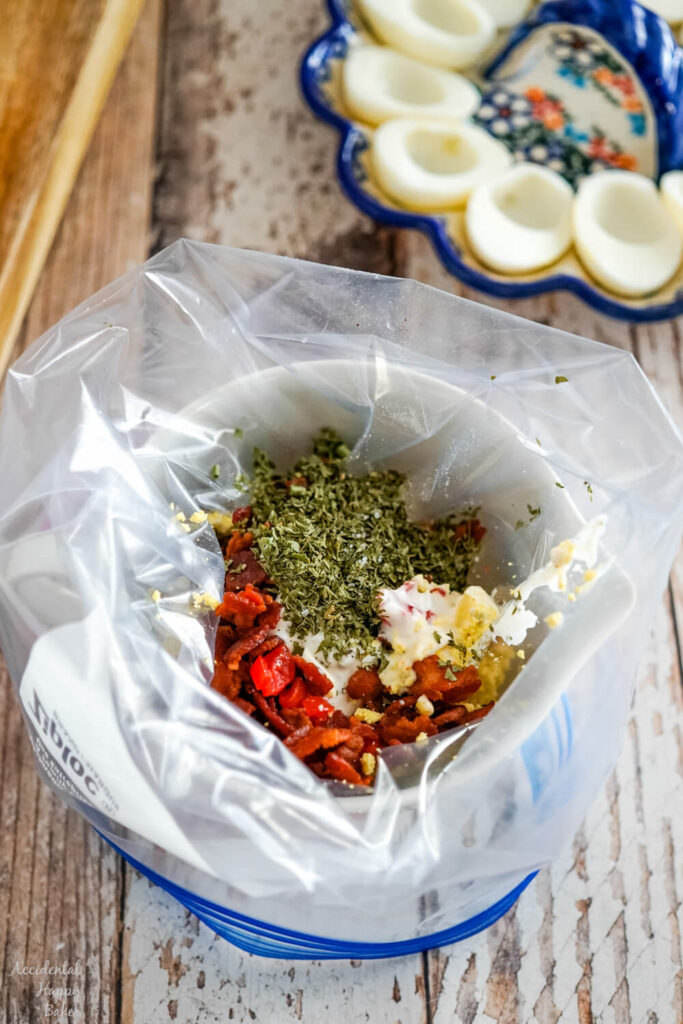 The ingredients for the BLT deviled eggs are added to a ziploc bag to combine.