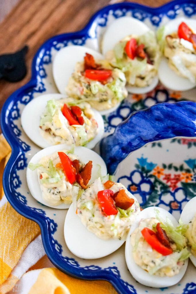 A close up image of BLT deviled eggs arranged on an egg plate.