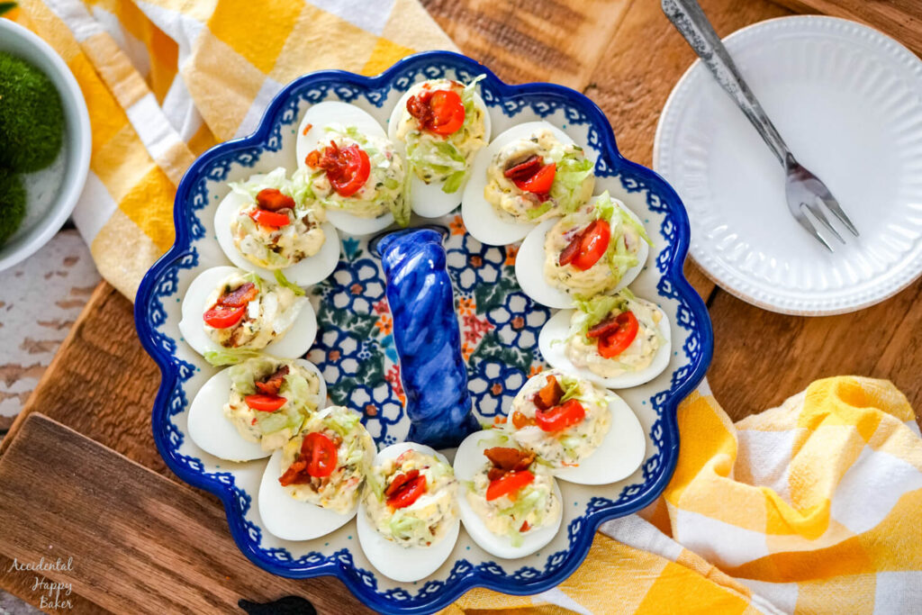 A plate of BLT deviled eggs on a wooden serving tray.