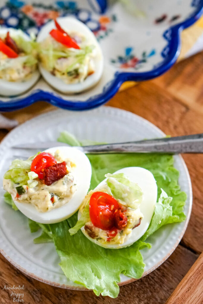 Two BLT deviled eggs on a bed of lettuce.
