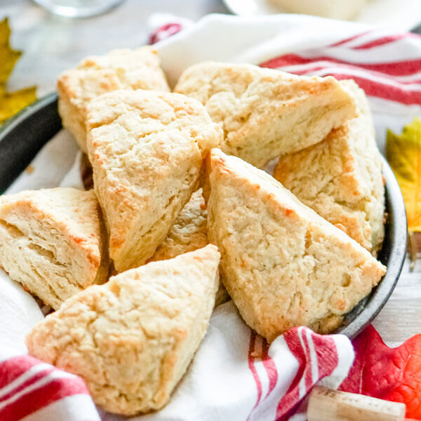 A pan full of white cheddar scones with a glass of wine in the background