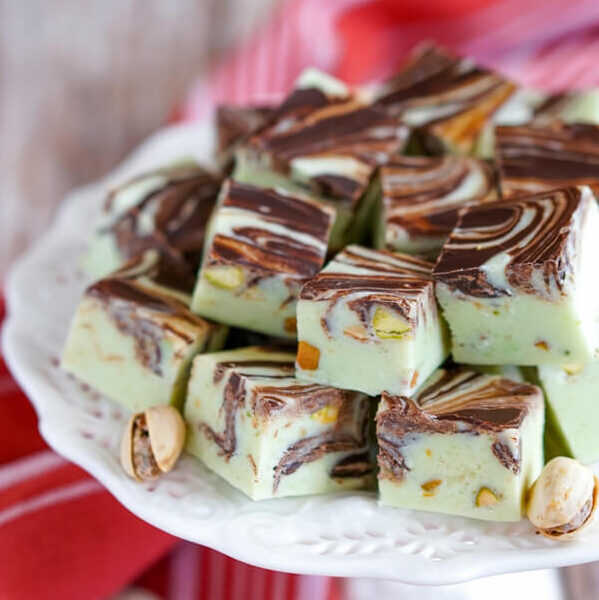 A white platter stacked high with Pistachio Swirl Fudge and pistachios.